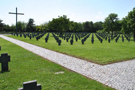 The Cross of Sacrifice and some of the many World War II and World War I graves at the Blumau German War Cemetery.