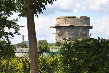 A round flak (anti-aircraft) tower in the Augarten Park in Vienna. This type of towers were called G-towers. The golden tower in the background is a part of a heating plant and trash incinerator.