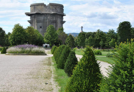 A round flak (anti-aircraft) tower in the Augarten Park in Vienna. The golden tower in the background is a part of a heating plant and trash incinerator.