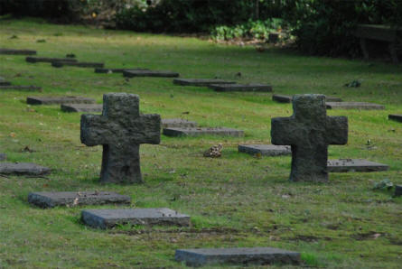 The Menen German War Cemetery is a typical German military cemetery - with dark grave stones lying flat on the ground and a few dark crosses.