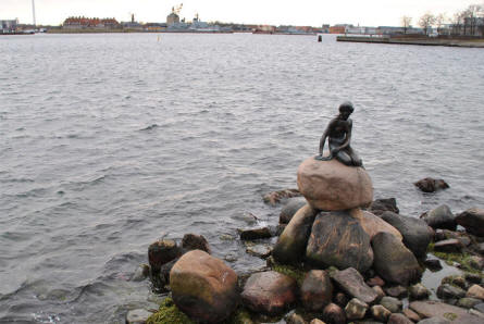 "The Little Mermaid in Copenhagen is located at the entrance to the central part of the Copenhagen harbour. This picture is taken towards the central part of the Copenhagen harbour. In the background the old Danish Naval Base ""Holmen"" can be seen."