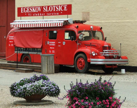 A vintage fire truck is used as an ice kiosk at Egeskov Castle.