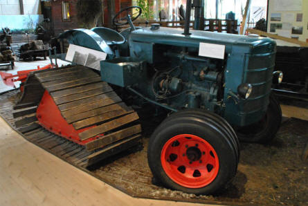 A vintage tractor displayed at the Stenvad Peat Digging Museum. This tractor was modified to be able to drive in the swampy bog areas where the peat is dug up.