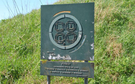 "A sign showing the layout of the old Viking fortress close to the Fyrkat Viking Centre in Hobro. The outer circle is earthwork (with 4 entrances) and the ""boxes"" inside the circle shows where the houses were located."