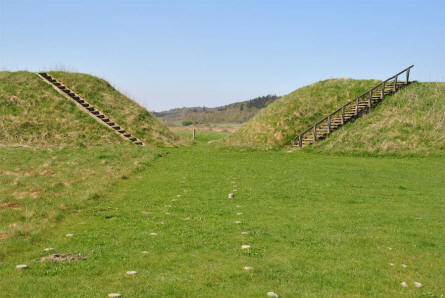 The earthwork of the old Fyrkat Viking fortress - as it looks today - looking from the inside thru one of the four entrances. The stones in the grass shows where the viking houses were located.