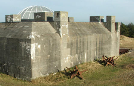 "The remaining main bunker of the Tripitz Battery with ""Czech Hedgehogs"" in from of it and gun parts at the end."