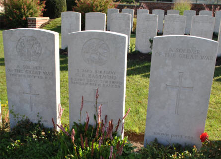 "The World War I grave of Serjeant G. E. Eastmond (killed on the 22nd of August 1918) at the Bapaume Post Military Cemetery just east of Albert. His grave is flanked by to ""unknown"" graves."