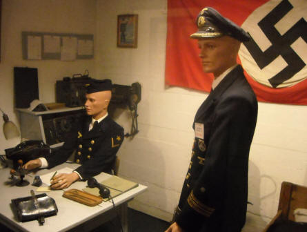German World War II uniforms and office environment displayed at the Calais War Museum.