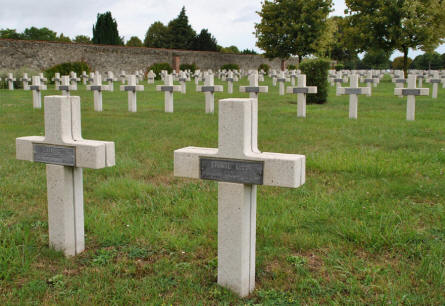 Some of the many World War I graves at the Suippes French War Cemetery. The civilian cemetery is just behind the wall to the left.