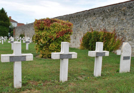 Some of the many World War I graves at the Suippes French War Cemetery. The civilian cemetery is just behind the wall to the right.
