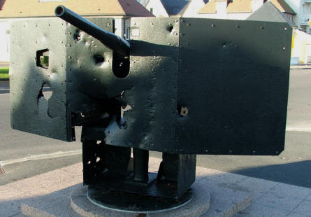 A small German canon located at a street in on of the small villages at the D-day coast. Notice the battle damage.