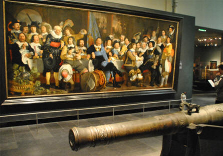 One of the many large classic painting displayed at the Rijksmuseum in Amsterdam. At the front a classic maritime canon.