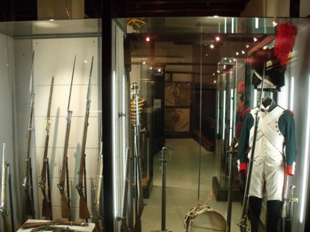 Uniforms and weapons from before 1900 displayed at the Italian War Museum in Rovereto.