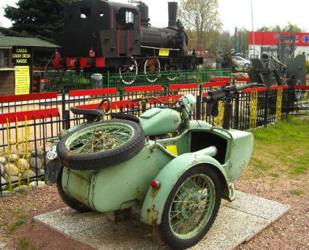 A vintage motorcycle and a steam locomotive displayed at the Museum Gottard Park.