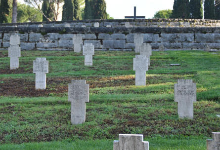 Some of the many World War II tombstones at the German War Cemetery in Caira - near Monte Cassino. Notice the cross of sacrifice on top of the hill.
