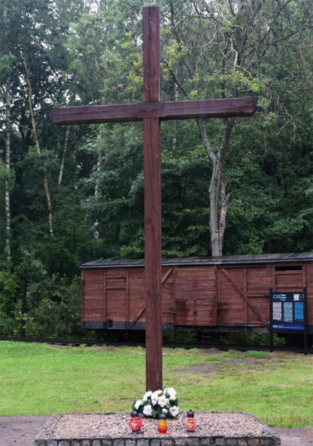 A memorial cross at the Stutthof Concentration Camp. In the background one of the railway wagons that was used to transport Jews and other prisoners to the camp.